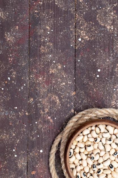 茶色の木製、食品生豆ハリコットにロープで茶色のボウル内の新鮮な生豆の上面図 無料写真