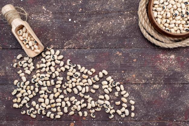 茶色の机全体に広がる新鮮な生豆の上面図、食品生豆ハリコット 無料写真