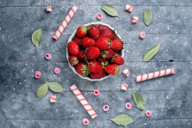 スティックキャンディーと灰色のフルーツベリーフレッシュキャンディースイートの緑の葉と一緒にプレート内の新鮮な赤いイチゴの上面図 無料写真