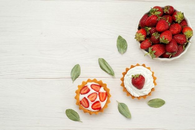 Вид сверху свежей красной клубники, спелых и вкусных ягод внутри белой тарелки с тортами на свету, ягодами красного цвета Бесплатные Фотографии