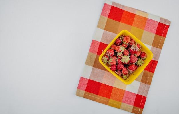 コピースペースと白の格子縞のナプキンに黄色のボウルに新鮮な熟したイチゴのトップビュー 無料写真