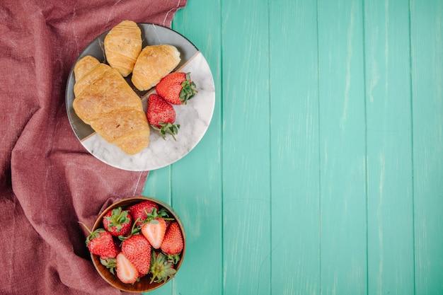 コピースペースを持つ緑の木の皿にクロワッサンと新鮮な熟したイチゴのトップビュー 無料写真