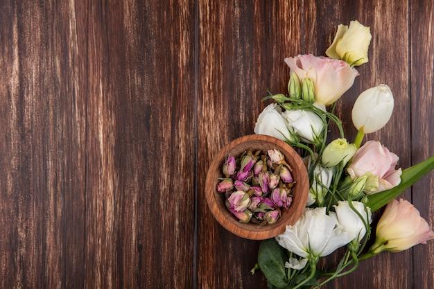 복사 공간 나무 배경에 나무 그릇에 장미 꽃 봉 오리와 신선한 장미의 상위 뷰 무료 사진