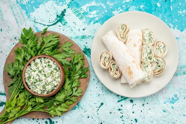 茶色のボウルの中に緑があり、明るい青色の机の上に野菜のロールが付いている新鮮なスライスしたキャベツのサラダの上面図、食品野菜サラダの鮮度スナック 無料写真