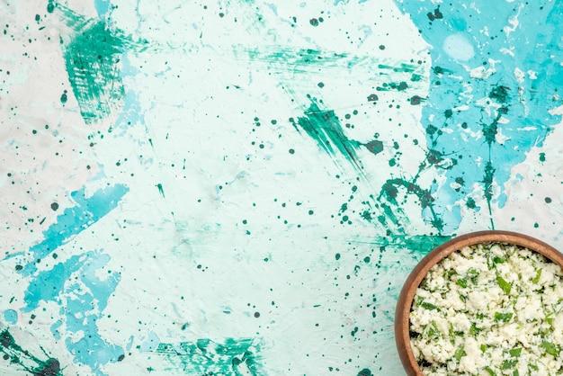 Вид сверху салата из свежей нарезанной капусты с зеленью в коричневой миске на ярко-синей, зеленой закуске из овощного салата Бесплатные Фотографии