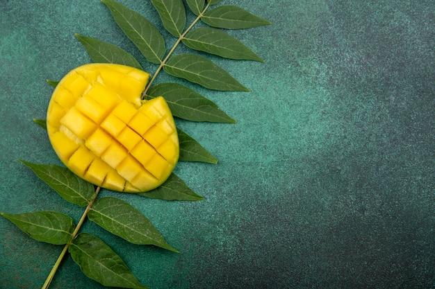 Вид сверху свежего нарезанного манго с листом на зеленом Бесплатные Фотографии