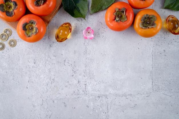 中国の旧正月の概念のための灰色のテーブルに葉を持つ新鮮な甘い柿柿の上面図、単語は春が来ることを意味します。 Premium写真