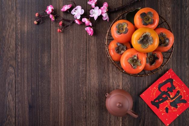 中国の旧正月の概念のための木製のテーブルに葉を持つ新鮮な甘い柿柿の上面図、この言葉は祝福が来ることを意味します。 Premium写真