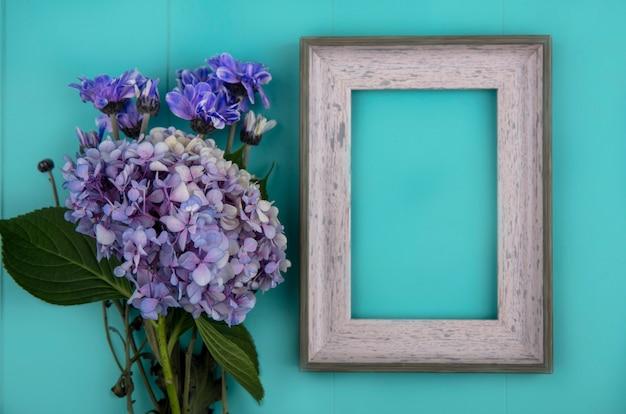 コピースペースと青い背景の上のデイジーやgardenziaなどの新鮮な素晴らしい花の上面図 無料写真