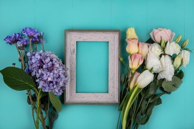 コピースペースと青い背景の上のバラのチューリップデイジーなどの新鮮な素晴らしい花の上面図 無料写真