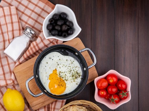 白いボウルにブラックオリーブとチェックのテーブルクロスと木のトマトの木製キッチンボード上のフライパンで目玉焼きのトップビュー 無料写真