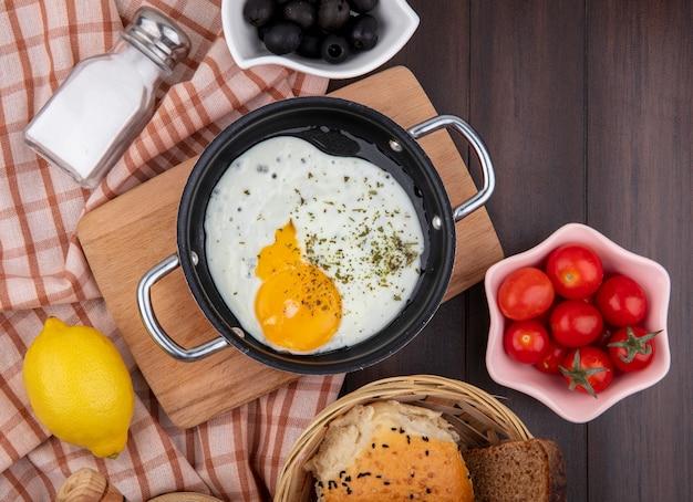 木のチェッククロスにブラックオリーブチェリートマトと木製キッチンボード上のフライパンの卵の平面図 無料写真