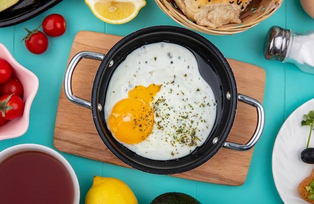 青のパンのバケツをレモンと木製キッチンボード上の鍋に目玉焼きのトップビュー 無料写真