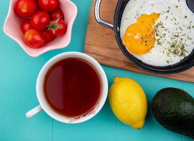 白いボウルにトマトと青にレモンと木製キッチンボード上の鍋に目玉焼きのトップビュー 無料写真