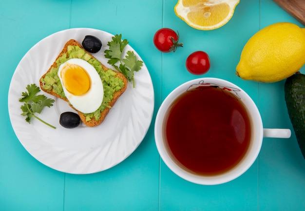 青の紅茶のカップとブラックオリーブと白いプレートにアボカドの果肉とパンのトーストスライスに目玉焼きの平面図 無料写真