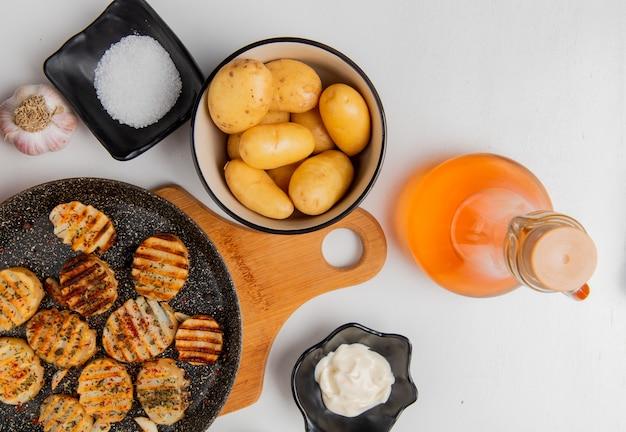 Вид сверху ломтики жареного картофеля в сковороде на разделочную доску с сырыми в миску чесноком растопленного сливочного масла майонез соль и черный перец на белом Бесплатные Фотографии