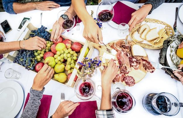 Вид сверху на руки друга, едящие еду и вино на вечеринке в саду барбекю Premium Фотографии