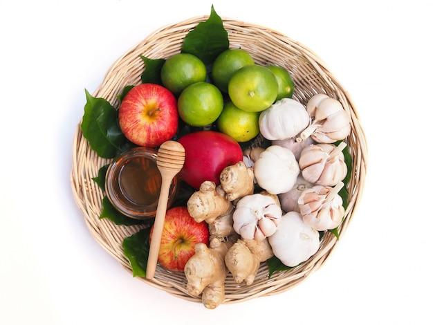 果物と野菜の白い背景で隔離の手に蜂蜜健康食品と竹かごのセットのトップビュー Premium写真