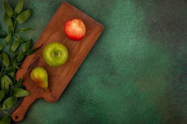 Вид сверху на фрукты как яблоко, персик, груша на разделочной доске с листьями на зеленом фоне с копией пространства Бесплатные Фотографии