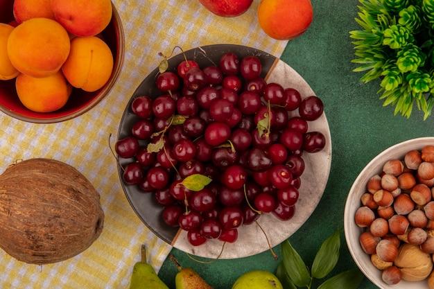 格子縞の布に梨とココナッツと緑の背景にナッツのボウルとプレートとボウルにサクランボとアプリコットとして果物の上面図 無料写真