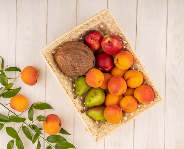 木製の背景の葉とバスケットのココナッツ桃梨として果物の上面図 無料写真