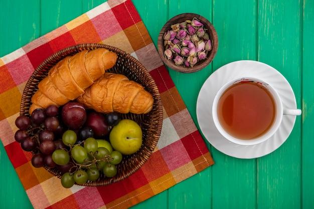 ブドウのプルオットとしての果物の上面図格子縞の布の上にバスケットにクロワッサンと花のボウルと緑の背景にお茶のカップと花のボウル 無料写真