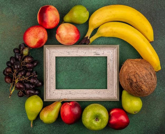 コピースペースと緑の背景のフレームの周りの桃ココナッツアップル梨バナナブドウとして果物の上面図 無料写真