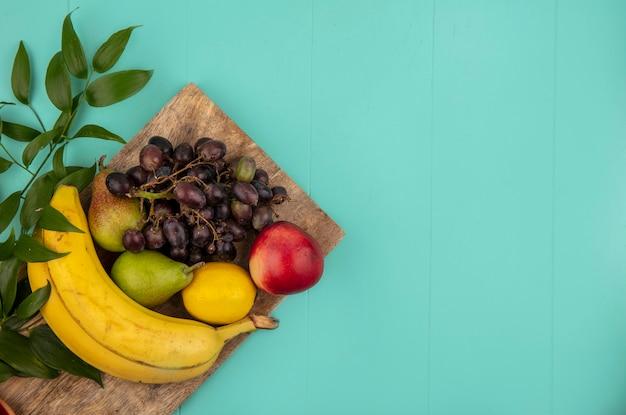 コピースペースと青い背景のまな板に葉を持つ桃梨レモンブドウバナナとして果物の上面図 無料写真