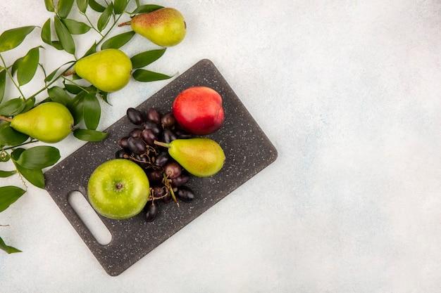 コピースペースと白い背景の葉とまな板上の梨リンゴブドウ桃として果物の上面図 無料写真
