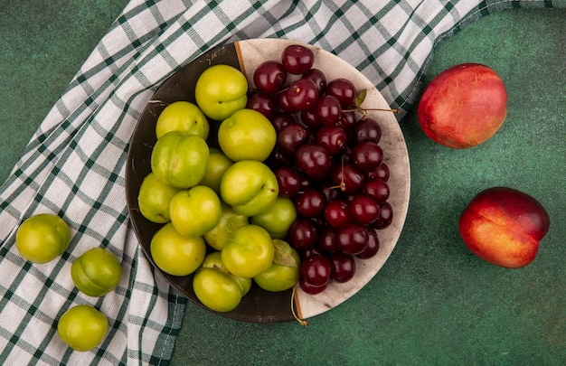 緑の背景に桃と格子縞の布のプレートに梅やさくらんぼとして果物の上面図 無料写真