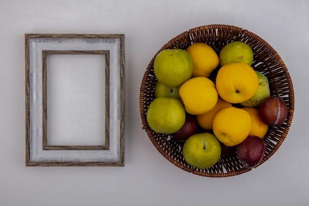 コピースペースと白い背景の上のフレームとバスケットのプルオットとネクタコットとして果物の上面図 無料写真