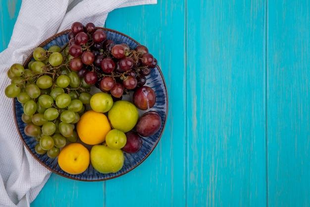 コピースペースと青い背景の上の白い布の上のプレートのプルオットネクタコットプラムとブドウとしての果物の上面図 無料写真