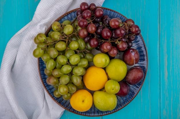 青い背景の上の白い布のプレートにプルオットネクタコットプラムとブドウとして果物の上面図 無料写真