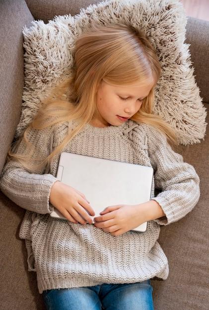 タブレットで寝ている女の子の上面図 無料写真