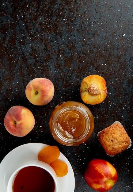 コピースペースを持つ黒と茶色の表面に桃のカップケーキと紅茶のカップと桃のジャムのガラスの瓶の平面図 無料写真