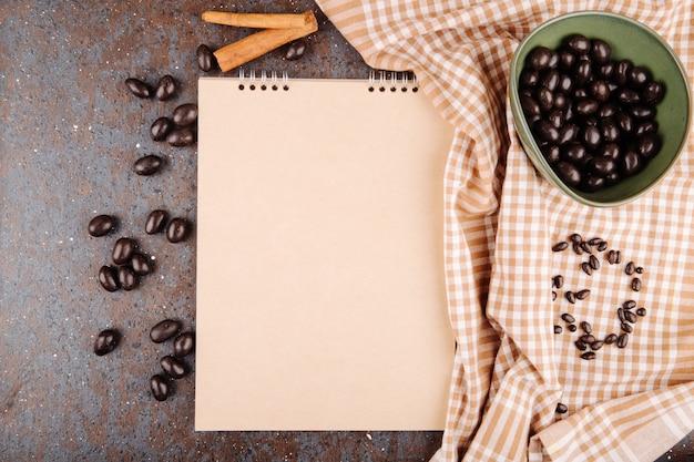 黒の背景にボウルとスケッチブックの艶をかけられたチョコレートナッツキャンデーのトップビュー 無料写真