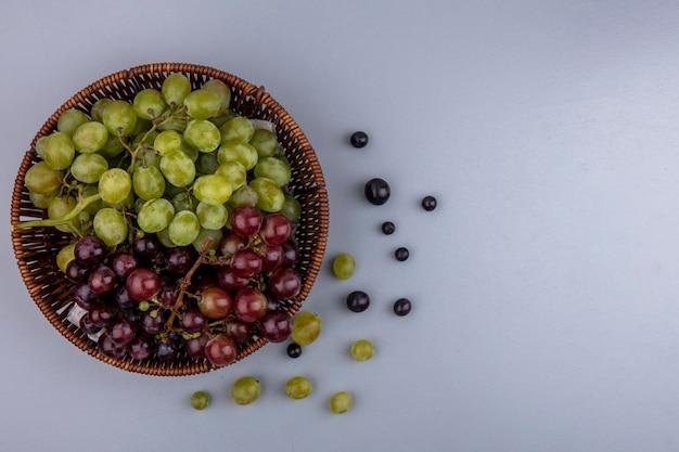 Вид сверху на виноград в корзине и узор из виноградных ягод на сером фоне с копией пространства Бесплатные Фотографии