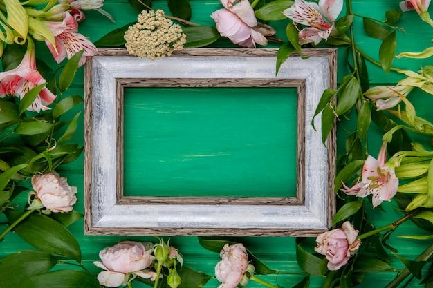 緑の表面に薄いピンクの花と葉の枝を持つ灰色のフレームのトップビュー 無料写真