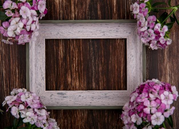 木製の表面に光のピンクの花を持つ灰色のフレームのトップビュー 無料写真
