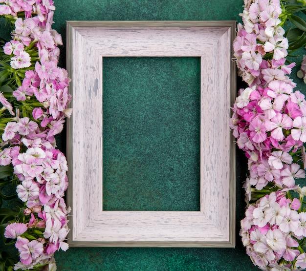 緑の表面に薄い紫の花を持つ灰色のフレームのトップビュー 無料写真