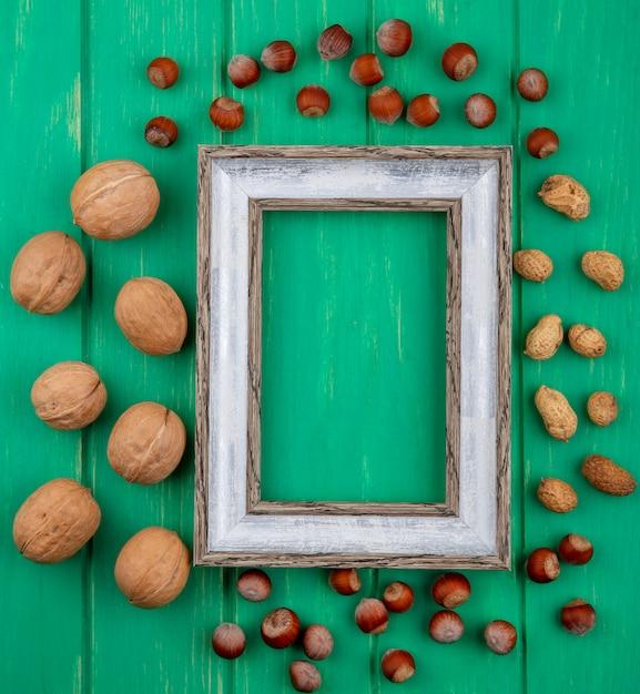 Вид сверху серой рамки с грецкими орехами, фундуками и арахисом на зеленой поверхности Бесплатные Фотографии