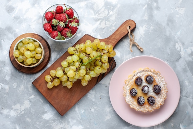 ライトデスク、フルーツケーキ新鮮なまろやかな夏に赤いイチゴと緑のブドウの上面図 無料写真
