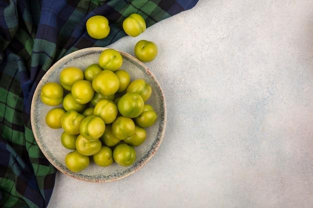 格子縞の布とコピースペースと白い背景の上のプレートの緑の梅のトップビュー 無料写真