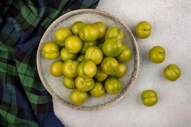 格子縞の布と白い背景の上のプレートの緑の梅のトップビュー 無料写真