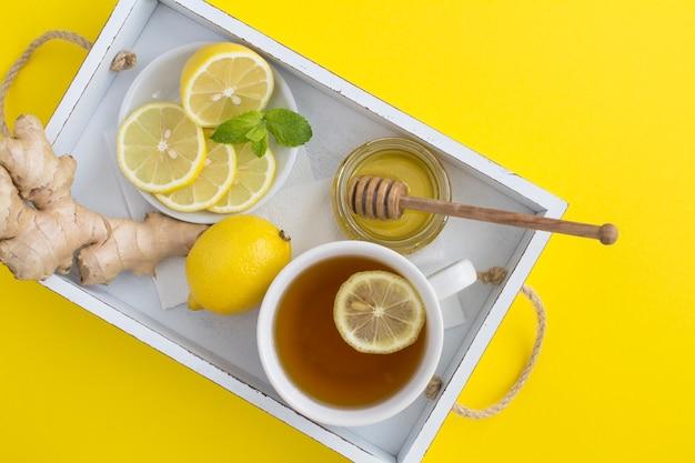 レモン、蜂蜜、生姜と黄色の白い木製のトレイに緑茶のトップビュー Premium写真