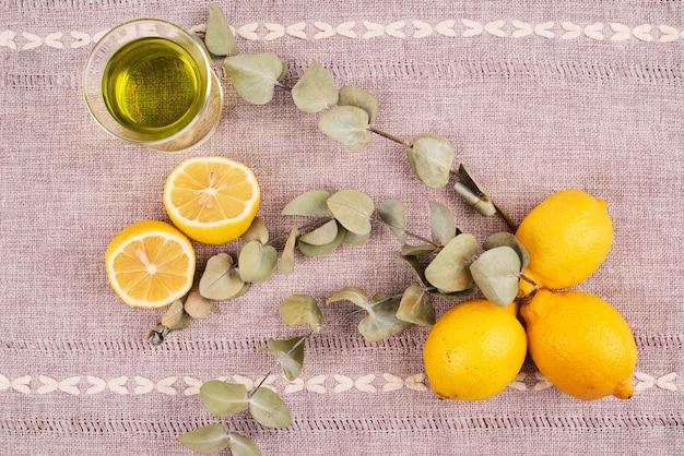 茶色のテーブルクロスにレモンと緑茶の上面図。 無料写真