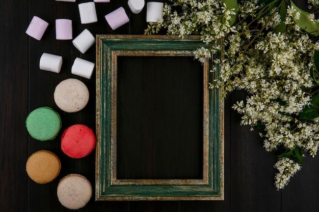 黒の表面にマシュマロマカロンと花と緑がかったゴールドフレームのトップビュー 無料写真