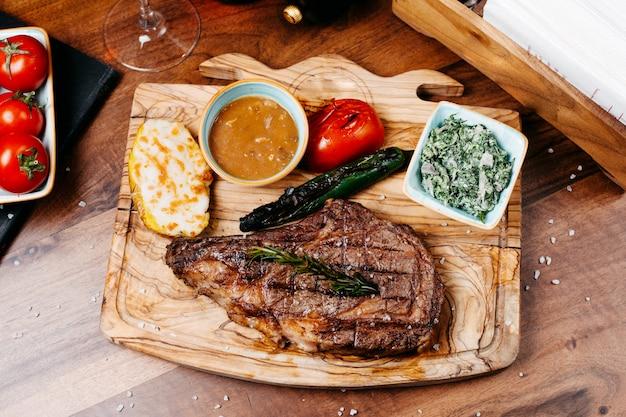 Вид сверху гриль стейк из говядины с овощами и соусом на деревянной доске Бесплатные Фотографии