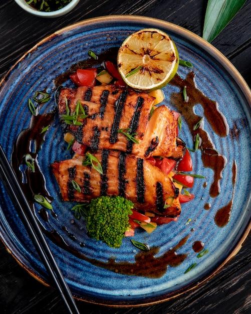 Вид сверху жареного лосося с овощами лимоном и соевым соусом на тарелку на деревянный стол Бесплатные Фотографии