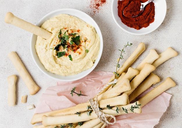 Вид сверху гриссини с хумусом и зеленью Бесплатные Фотографии